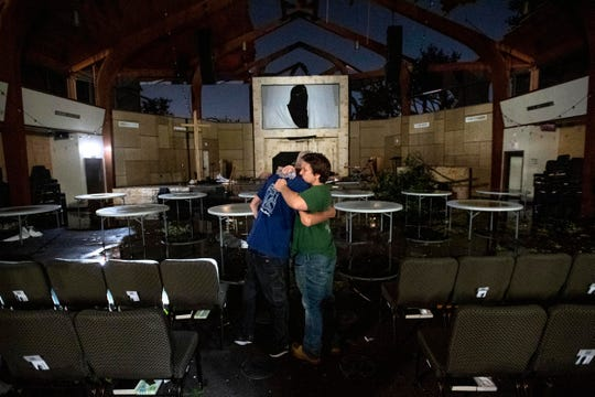 Matt Younger, right, a pastor at Northway Church, embraces facilities associate Robert Lusk in their church's severely damaged sanctuary after a tornado tore through North Dallas.