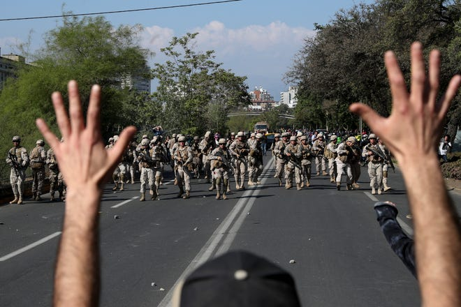 A demonstrator holds up his hands toward advancing soldiers during a protest as a state of emergency remains in effect in Santiago, Chile, Sunday, Oct. 20, 2019. Protests in the country have spilled over into a new day, even after President Sebastian Pinera cancelled the subway fare hike that prompted massive and violent demonstrations.