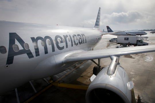 FILE - In this Feb. 26, 2014 file photo, an American Airlines Airbus A319 is parked at a gate at Philadelphia International Airport.