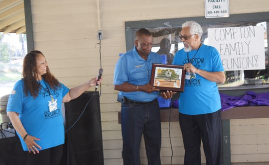 Honored at the reunion with a plaque by Compton family member Harold Hines (far right) was Pineville mayor Clarence Fields who said he and his twin sister were raised by his foster mother, Ida Compton. To the left is Karen Compton Ward.