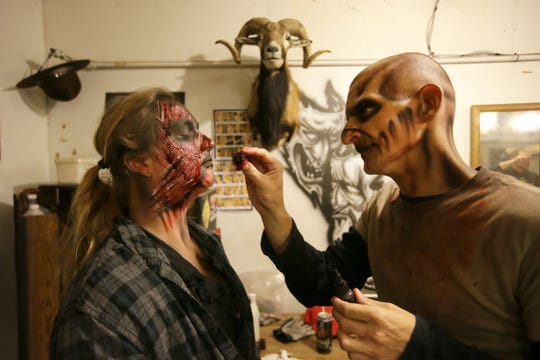 Bryce Cook applies makeup to Melanie Zellner as the Burial Chamber is open for the season in 2017.