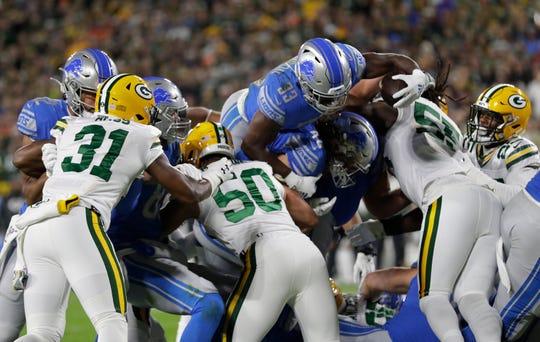 Kerryon Johnson runs against the Packers earlier this season.