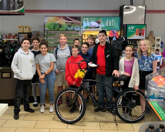 Billy Stump (right center) stands with his new bike and a group of neighborhood kids who presented it to him.