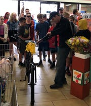 Longtime clerk Billy Stump receives a new bike from customers at the West Long Branch 7-Eleven.