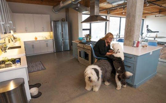 Sawtooth Group, president and CEO Kristi Bridges plays with her dogs during a break from work in the kitchen area of office. They are on the fourth floor of the building.The Sawtooth Group, a digital marketing firm in Red Bank, is the first tenant to move into the Anderson Building, a former warehouse that has become one of the hottest properties in Red Bank.