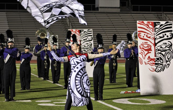 "Megan Colwell of the Wylie High flag corps balances her flag on her chest during the band's Region VI marching band performances Monday night at Bulldog Stadium. Wylie earned a ""1"" rating to advance to the regional competition.' Oct 21 2019"