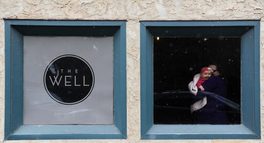 Zoe Ott laughs watching the snow fall as her grandmother Bernita Sheets holds her near the window during a church service inside the former home of The Leaf on March 2, 2014. The group, called The Well, meets at the corner of Cypress and North Second streets.