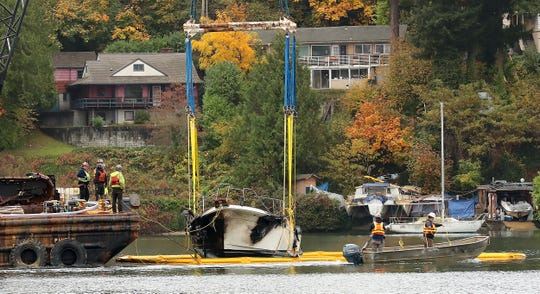 Salvage and crane crews begin lifting Mike and Jamie Babbitt's charred boat out of the water in front of the Bremerton Yacht Club on Tuesday.