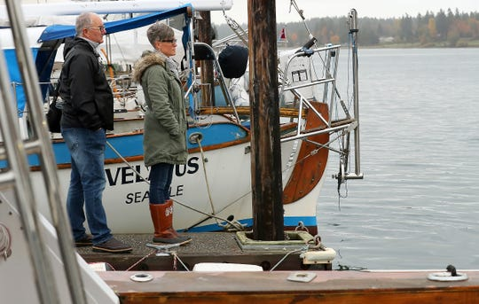 Mike Babbitt and his wife, Jamie, look on from the end of the dock as the crane moves into position to begin lifting their boat out of the water in front of the Bremerton Yacht Club on Tuesday. A fire broke out aboard Mike and Jamie Babbitt's boat on Sept. 27. Mike and their two-dogs escaped the fire and the boat eventually sank in front of the marina.