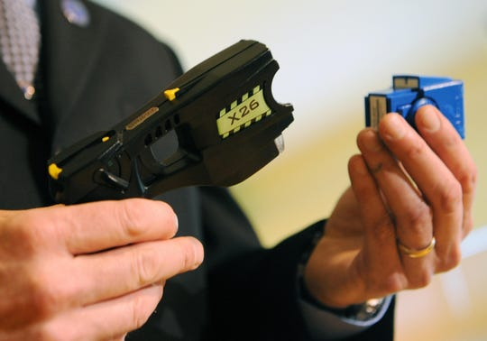 """Thomas Smith, president of  Taser International, a US-based manufacturer of law enforcement equipment, displays in Singapore the X26 """"electronic control device."""" The same model was used on Gregory Lloyd Edwards shortly before his death in December 2018."""