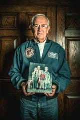 Astronaut Charlie Duke holding a copy the family picture that he left on the moon in 1972.