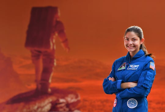 Alyssa Carson standing in front of a Mars mural at the Kennedy Space Center Visitor Complex. Carson, 18-year-old Florida Tech student, has known she wanted to be an astronaut from a very young age and has been working towards that goal since childhood.