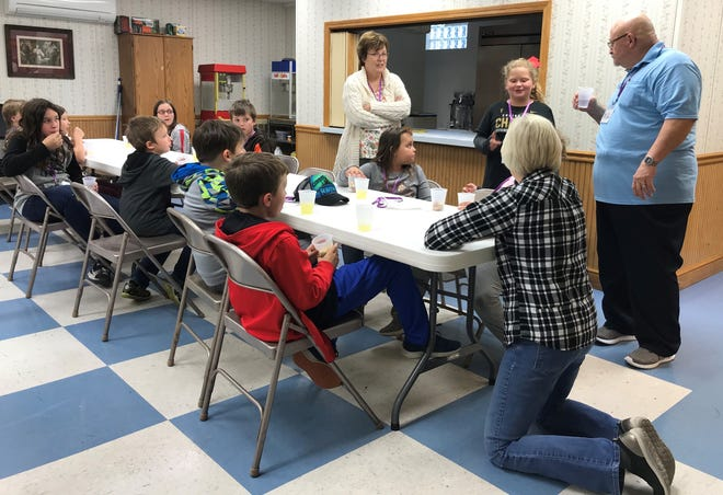 Teacher Bob Laipply, right, volunteers and students listen as a girl recites the names of the books of the Bible during a King's Kids meeting on Friday.