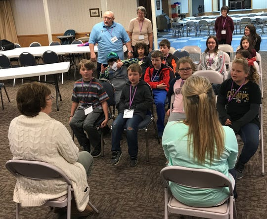 Kids, teachers and volunteers prepare to sing a song during a King's Kids meeting on Friday.