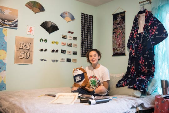 Vivian Dennis, 15, from Greenfield, sits on her bed surrounded by many of the Japanese mementos either given to her or received while spending two months in Japan as part of an exchange program offered through the Ohio 4-H State Office and its Japanese partner, Labo.