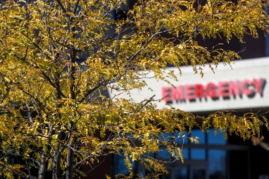 The sign for the emergency care entrance is obscured by leaves changing color at Tennova Healthcare in Clarksville, Tenn., on Tuesday, Oct. 22, 2019.