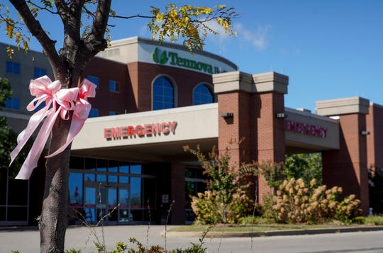 A pink bow placed on a tree blows in the wind outside the emergency care entrance at Tennova Healthcare-Clarksville on Oct. 22, 2019.