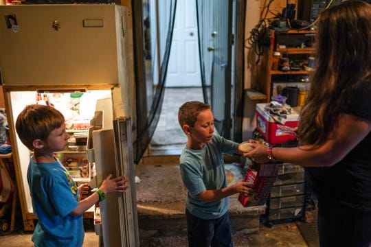 (Right to left) Angela Peters, 32, of Commerce Township gets snacks out for her sons Gabriel Peters, 5, and Dante Hilton, 7, after they arrived home in Commerce Township on Monday, October 21, 2019 from school at Keith Elementary School. Peters says her children often come home wanting snacks due to the lack of time they have to eat and have recess at their school.