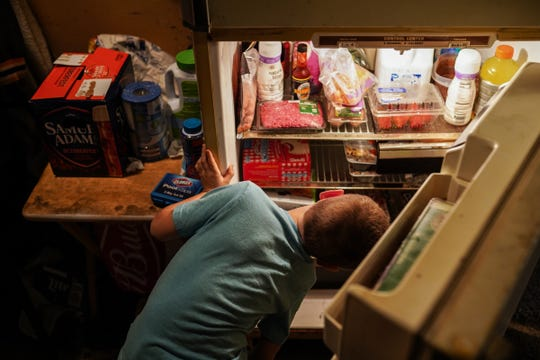 Gabriel Peters, 5, of Commerce Township looks through the refrigerator for snacks on Monday, October 21, 2019 after returning home from school at Keith Elementary School. Angela Peters says her children often come home wanting snacks due to the lack of time they have to eat and have recess at their school.
