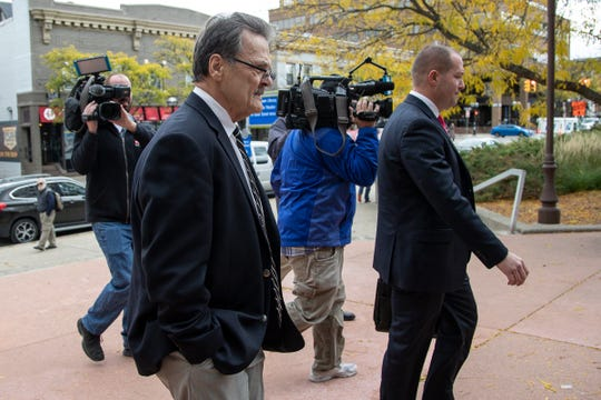 Former UAW official Jeffery Pietrzyk, center, next to his attorney Robert Singer, walks into the federal building in downtown Ann Arbor Tuesday before pleading guilty to charges connected to the ongoing UAW corruption probe.