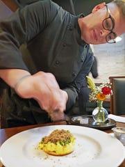 Executive Chef Jordan Whitemore shaves Burgundian black truffle onto Escoffier scrambled eggs at Savant in Midtown.