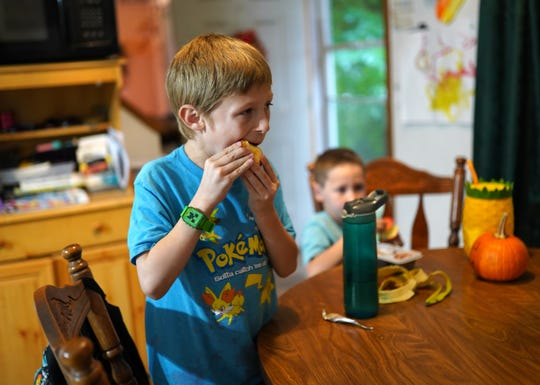 Dante Hilton (left), 7, eats an apple after returning home with his brother Gabriel Peters, 5, in Commerce Township on Monday, October 21, 2019 from school at Keith Elementary School. Peters says her children often come home wanting snacks due to the lack of time they have to eat and have recess at their school.