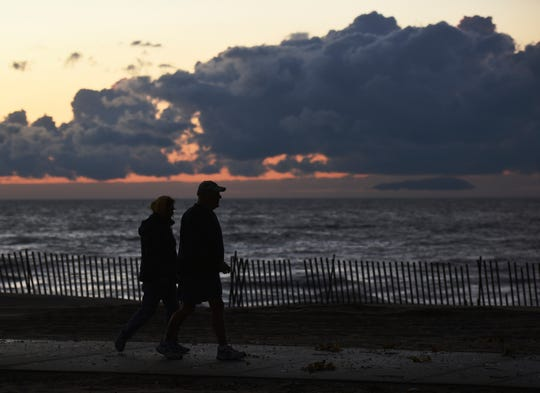 A couple stroll along Silver Beach in St. Joseph, Mich., Monday, Oct. 21, 2019, as a storm front moves over Lake Michigan.