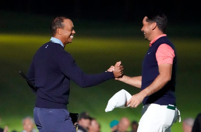 Tiger Woods of the United States, left, and Jason Day of Australia, right, hold their hands on the 18th hole after the skins challenge Monday in Japan.