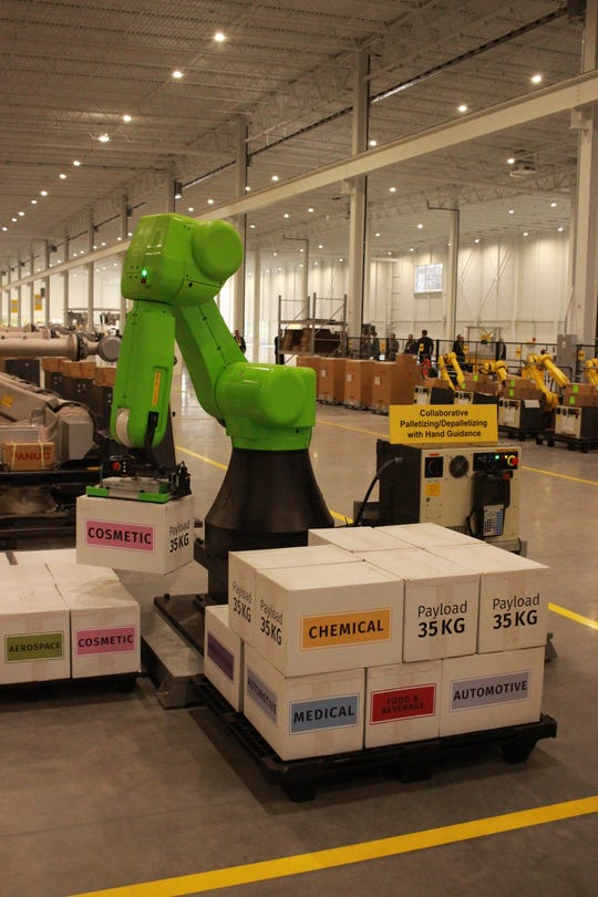 A FANUC cobot, built to work safely with humans, shows off its ability to gently move boxes