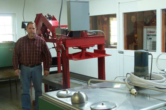 Chris Buerge, who along with his wife Marla, own the Apple Barrel Cider Mill in Ithaca, Mich., shows off the mill's apple press where their son Corey makes his award winning cider.