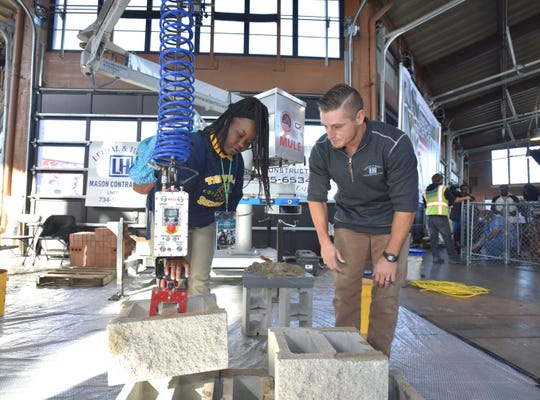 Leidal & Hart Mason Contractors mason foreman Nick Martin, of Flat Rock, teaches East English Village Preparatory Academy senior Quinise Anderson, 17, of Detroit, how to pick up a 65-pound cement block with this electric, robotic arm.