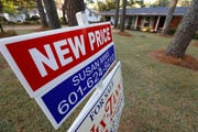 This Sept. 25, 2019, photo shows a sign indicating a new selling price for a house sits atop a realtor's sign in Jackson, Miss. On Tuesday, Oct. 22, the National Association of Realtors reports on sales of existing homes in September.