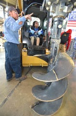 American Fence & Supply Co., Inc. foreman Tom Corriveau, of Algonac, talks to East English Village Preparatory Academy sophomore Jemaria Morgan, 15, of Detroit, about this CAT 259D skid steer with an 18-inch auger.