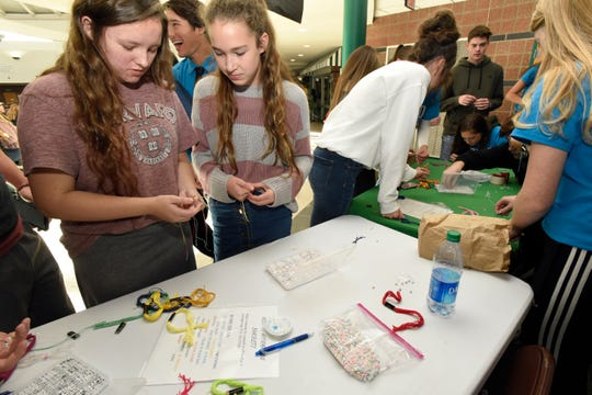 Lake Orion High School students work on making bracelets with positive messages for either themselves or for friends.