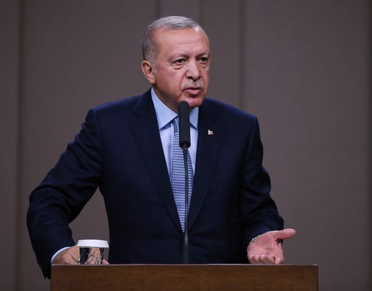 Turkish President Recep Tayyip Erdogan talks to reporters before traveling to Russia to meet with Russian President Vladimir Putin, in Ankara, Tuesday, Oct. 22, 2019.