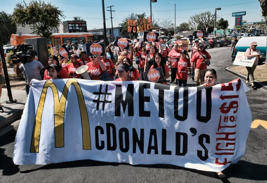 In this Sept. 18, 2018, file photo, McDonald's workers carry a banner and march towards a McDonalds in south Los Angeles.