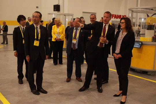 FANUC America President and CEO Mike Cicco showed Michigan Governor Gretchen Whitmer, right, the new Auburn Hills facility as FANUC President and CEO Kenji Yamaguchi, left, looks on