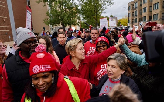 Elizabeth Warren called for people to support striking Chicago teachers after joining educators picketing outside an elementary school on Tuesday.