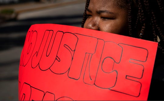 "Kimiko Brown of Evansville raises awareness of the killing of her brother, Laren Hall, on Oct. 13, 2019, by holding a sign stating ""No Justice, No Peace"" outside the Civic Center in Downtown Evansville Tuesday afternoon. Hall was shot during an apparent altercation behind Sportsman's Grille & Billiards on Evansville's West Side Oct. 13, 2019, shortly after midnight. The Evansville Police Department is investigating the shooting as a self-defense case and the person who pulled the trigger has not been arrested."