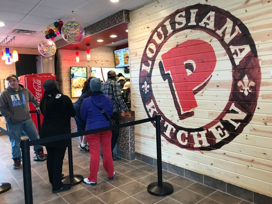Customers wait in line to get some of the first meals made at Popeyes Louisiana Kitchen on Tuesday, Oct. 22, 2019.