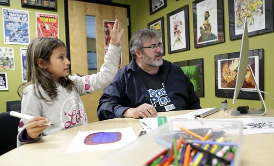 Craig Knitt, graphic arts director for the Boys & Girls Club of Greater Green Bay youth arts initiative, works with student Emalynn on a comic she created during a class on Oct. 17, 2019 at the west-side club on Oneida Street in Green Bay, Wis.