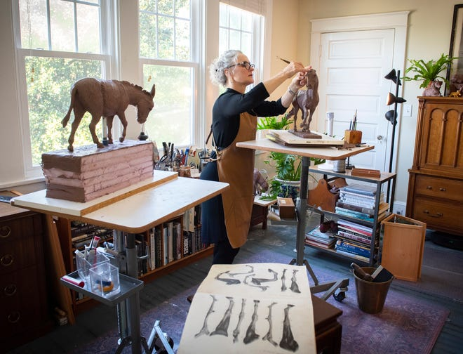 Artist Ann Malphrus works on a sculpture of a horse in her home studio in Greenville.