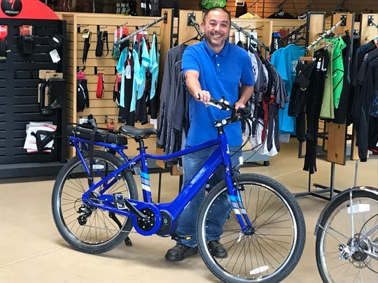 Knicker Biker store manager, Jason Rosales, displays one of the e-bikes for sale at the Great Falls store