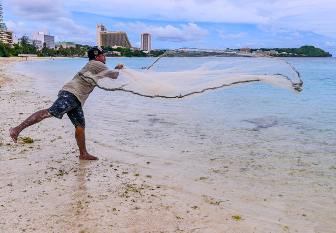 In this file photo from October 2019, talayeru (cast-net) fisherman Joaquin Villagomez sends his net into the waters of Tumon Bay targeting a small school of mañahak, or juvenile rabbit fish.