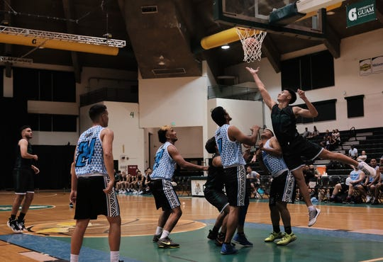 Tritons guard Michael Quan leaps above Four Stars defenders to put a shot in the net.