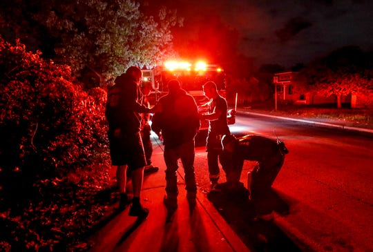 8:50 p.m. — Firefighters from Indianapolis Fire Station No. 20 help a man to his feet after concerned citizens found him passed out in the street on Wednesday, Oct. 16, 2019.