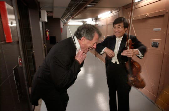 This June 13, 2003, file photo shows Conductor Laureate Raymond Leppard (left) laughing with Concertmaster Hidetaro Suzuki before they go on stage.