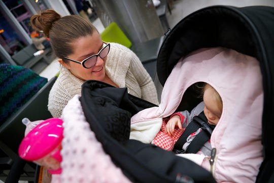 """6:22 a.m. — Samantha Perez watches her baby, Maddie Pryce, sleep at the Julia M. Carson Transit Center, Wednesday, Oct. 16, 2019, as they wait for their bus. """"She's dreaming,"""" says Perez as she watches Maddie twitch.  Perez takes the bus to the Excel Center, where she is working for her Core 40 diploma. Maddie will go to day care at the center."""