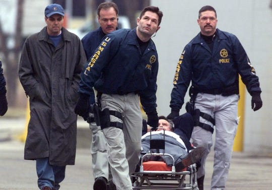 Gregory J. Dixon right on stretcher is wheeled away from the Indianapolis Baptist Temple by federal Marshals as son Gregory A. Dixon left walks alongside.  The 92-day siege came to an end at roughly 8:40 a.m.  Feb. 13, 2001.