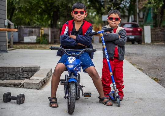1:55 p.m. — Luis, 8, and Timothy, 4, pose for a photo while playing with their bike and scooter at their home off East New York Street on the city's east side on Wednesday, Oct. 16, 2019.